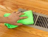 picture of floor heating  - Horizontal photo of female hand cleaning outside grill plate of heater floor vent with Red Oak Floors in background - JPG