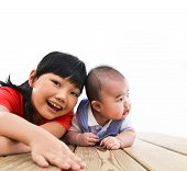 Little girl with baby laying on the wooden floor from top