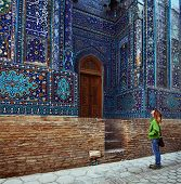 Young lady tourist watching ancient ornament of ancient complex of Shah i Zinda. Samarkand, Uzbekistan
