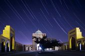 Night sky with star trails and oriental buildings of Poi Kalyan complex. Bukhara, Uzbekistan