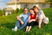 Portrait of a happy family of three on the lawn on front of their house