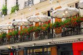 Paris cafe with a balcony patio and umbrellas