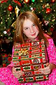 Young girl holding a big Christmas present sitting under a Christmas tree