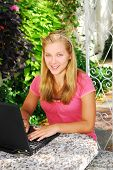 Smiling teenage girl typing on a portable computer outside