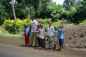 Dark Skinned African Children Crossing The Road, Tanzania.