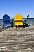 Painted wooden chairs on dock at a lake