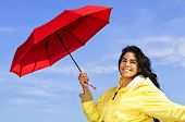 Portrait of beautiful girl wearing yellow raincoat holding red umbrella on windy day