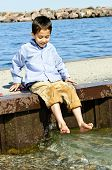 Portrait of young boy dipping feet in lake from pier