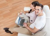 Young Couple Using Laptop In Couch