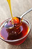 Thick golden honey drizzling onto spoon and bowl