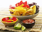 Bowl of salsa with colorful tortilla chips and lime