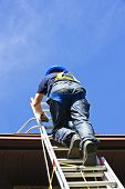 pic of descending  - Construction worker climbing extension ladder to roof - JPG