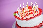 picture of uncut  - Birthday cake with burning candles on a plate on pink background - JPG