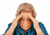 stock photo of embarrassing  - Elderly woman touching her head for headaches - JPG
