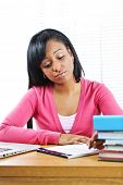 Young black female student studying at desk looking sad