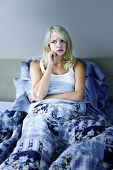 Sleepless blonde woman in bed with insomnia