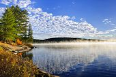 Foggy lake shore at sunrise in fall,  Lake of Two Rivers, Ontario, Canada