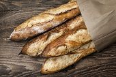 image of whole-wheat  - Four baguette bread loaves in paper bag on wooden background - JPG