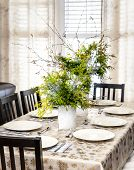 Dining table decorated for Christmas with eight place settings and evergreen centerpiece