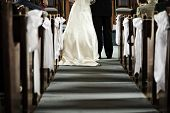 stock photo of pews  - Bride and groom getting married in church view from aisle - JPG
