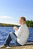 Young woman sitting with beverage on rock relaxing by beautiful lake in Algonquin Park, Canada