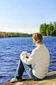 Woman sitting on rock relaxing by beautiful lake in Algonquin Park, Canada.