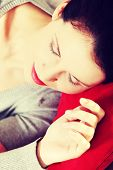 Closeup portrait of a young beautiful woman hugging to a red pillow, holding her hend next to the fa