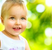 Little Baby Girl Portrait outdoor. Cute Child over nature background. Smiling adorable one year old baby close up. Sunny day