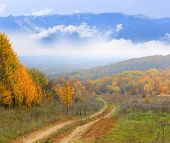 rut road in autumn forest against mountains in clouds background