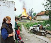 VUCITRN, KOSOVO - JUNE 26: Recently returned ethnic Albanians watch as the home of a Serb family bur