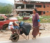 PEC, KOSOVO, 27 JUNE 1999 --- A Gypsy woman and her child flee recently returned Albanians seeking r