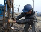 BAKU - AZERBAIJAN - JAN. 31: A roughneck grapples with a drilling rig in an oil production field nea