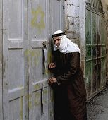 HEBRON - JANUARY 7: An Arab shop owner closes up for the day in the contested city's souk bazaar in Hebron, on January 7, 2000. Israeli graffiti on the door tells Arabs that