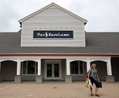 WOODBURY COMMON - JULY 9: Shoppers walk past a Ralph Lauren Polo retail clothing outlet store in Woo