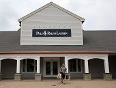 WOODBURY COMMON - JULY 9: Shoppers walk past a Ralph Lauren Polo retail clothing outlet store in Woodbury Common, New York, on Tuesday, July 9, 2013.