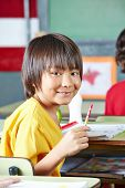 Japanese boy smiling in elementary school class at his desk