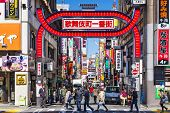 TOKYO, JAPAN - MARCH 15, 2014: Crowds walk below the Kabuki-cho signs. The area is a renown nightlif