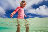 Adorable little girl at shallow water on tropical beach