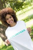 Portrait of smiling environmentalist holding volunteer tshirt in park