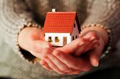 stock photo of house rent  - Woman holding a small new house in her hands - JPG