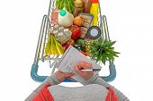 Overhead photo of a woman checking her shopping list with a trolley full of fresh food, isolated on