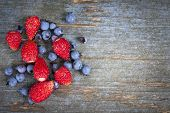 Wild strawberries and blueberries on old blue wooden background with copy space