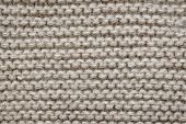 Knit texture of undyed natural brown alpaca wool knitted fabric with garter stitch pattern as backgr