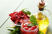 Sun dried tomatoes in glass jar, olive oil in glass bottle, basil leaves on color wooden background