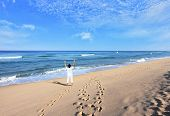 Middle-aged woman dressed in white doing yoga. Huge beautiful beach on the Atlantic coast. The seas