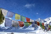 buddhist praying flags high in himalayan mountains