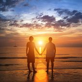 Happy young couple holding hands on sea beach during the beautiful sunset.