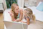 Cute little girl and mother on bed using laptop at home in the bedroom