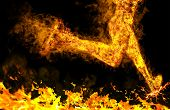 foto of fieri  - Fiery running man with motion effect on black - JPG