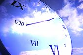 Digitally generated roman numeral clock on blue sky background